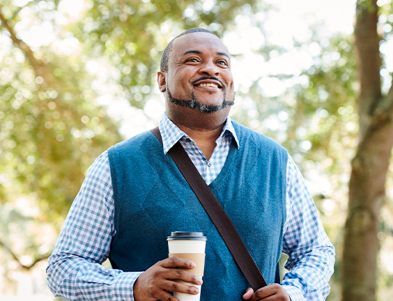 Man holding coffee cup and smiling